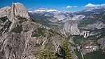 A view from Glacier Point, Yosemite National Park, of the iconic geographic landmarks Cloud's Rest, Half Dome, Nevada Falls, and Vernal Falls: early summer, bright blue skies, scattered white clouds.