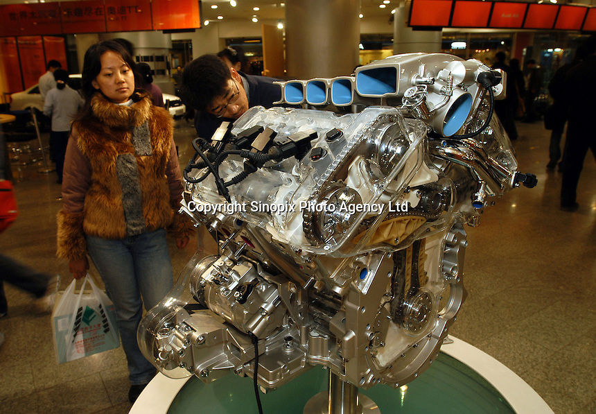 "Potential customers examine a dummy engine of an imported ""Phaeton"" in the VW's Oriental Plaza show room.."