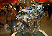 """Potential customers examine a dummy engine of an imported """"Phaeton"""" in the VW's Oriental Plaza show room.."""