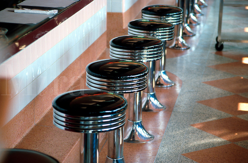 Row of black & chrome stools at the counter of a diner.