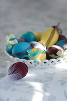Sunlight falls on a ceramic dish filled with coloured eggs tied with ribbon