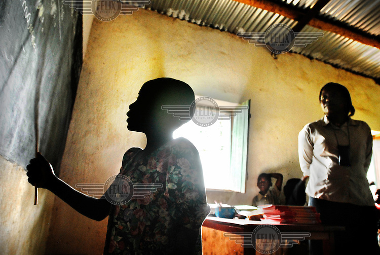 Child and teacher at the blackboard in a classroom at the Public Primary School of Butamwa. This school has 985 students, but only 17 teachers. The parents have to pay school fees for their children, up to $3 per trimester, but many struggle to pay this.