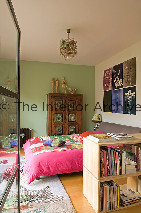 This colourful bedroom has a bright pink duvet cover, green walls and mix of furniture and artwork