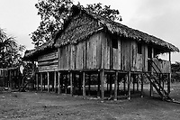 A wooden house on piles built by settlers deep in the Amazonia region of Colombia, 26 April 2004. Amazonia is the world's largest dense tropical forest area. Since the 16th century the original indigenous people have been virtually pushed away or exterminated. The primal ancient unity between tribes and the jungle ambient has changed into a fight between the urban based civilization and the jungle enviroment. Although new generations of white and mestizo settlers have not become adapted to the wild tropical climate and rough conditions, they keep moving deeper into the virgin forest. The technological expansion causes that Amazonia is changing rapidly.
