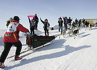 Race fans cheer on Aliy Zirkle as she runs up the ramp from the Bering Sea into Nome.