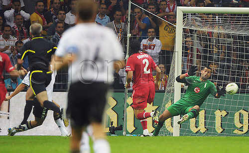 07.10.2011 Istanbul Turkey.  Germany's Mario Gomez (hidden) scores the 1-0 against goalkeeper Volkan Demirel (R)of Turkey vie for the ball during the EURO 2012 qualifying match between Turkey and Germany at the Turk Telekom Arena.