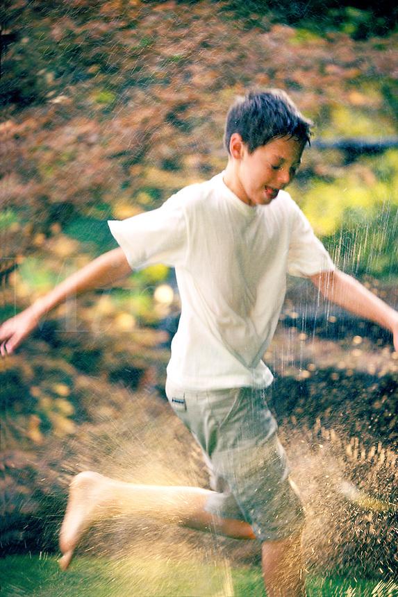 Teen boy playing in the summertime sprinklers