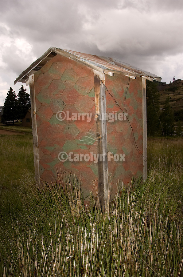 Asphalt shingled covered outhouse, storm in the Colorado Rockys