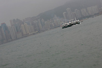 A Star Ferry used for public transportations passes the quarter of Causeway Bay on the East of the Island of Hong-Kong, in the fog.