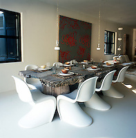 A large dining table made from an old tree surrounded by Verner Panton chairs dominates the dining area. 'Johnny B Good' pendant lamps by Ingo Maurer hang above the dining table with an abstract painting by Sophie de Garam behind.