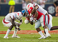NWA Democrat-Gazette/BEN GOFF @NWABENGOFF<br /> Joe Foucha (left), Arkansas free safety, and Mataio Soli, Arkansas defensive end, tackle Scottie Phillips, Ole Miss running back, in the first quarter Saturday, Sept. 7, 2019, at Vaught-Hemingway Stadium in Oxford, Miss.