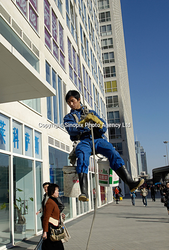 Chinese cleaners wipe the glass wall of Jianwai SOHO, Beijing, China..