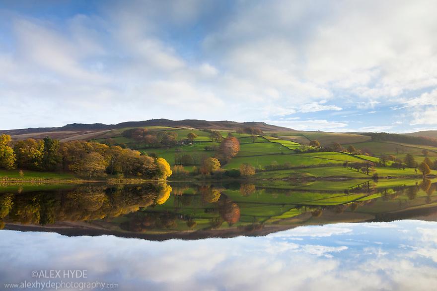 Ladybower Reservoir showing mirror reflections on a calm autumn morning. Peak District National Park, Derbyshire, UK. November.