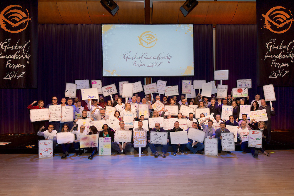 Large group photo of all of the leadership forum's participants displaying their signage.