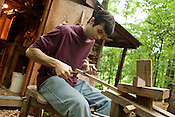 May 19, 2010. Pittsboro, North Carolina.. Elia Bizzarri makes rocking chairs the old fashioned way, by hand, using tools whose design date back hundreds of years. Working out of a shop in the woods outside Pittsboro, he takes 30 to 45 hours to make each hand crafted chair.. Using a shaving horse, Bizzarri shapes a spindle for the back of a rocking chair with a draw knife.