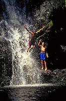 Young boys have a great time  jumping off a waterfall on the Big Island of Hawaii.