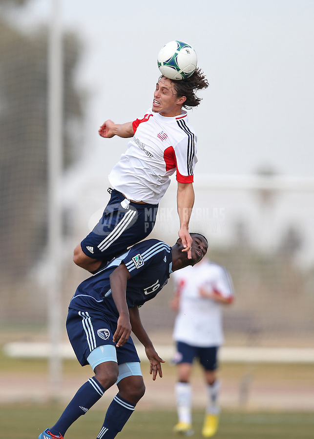 Jan. 25, 2013; Casa Grande, AZ, USA: New England Revolution midfielder Ryan Guy (top) leaps over Sporting KC midfielder Peterson Joseph (19) as he goes for a header during a preseason game at Grande Sports World. Mandatory Credit: Mark J. Rebilas-USA TODAY Sports
