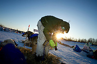 Rookie musher Kelly Maixner boots his team as he prepares to leave the ghost-town checkpoint of Iditarod as the sun rises on Friday morning during the 2011 Iditarod race.