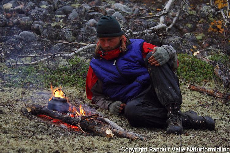 Betenkt mann sitter ved lite bål ---- Man sitting by small fire