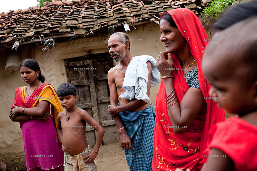 "(L-R) Dharma (18, soon to be married), Akanksha (8), Tribhuvan Adivasi (50), Kelaji Adivasi (45), and Vinita's (23, married when 14, has 3 children) baby. Tribhuvan, a farm labourer, says that ""it was a mistake to have so many children. Food is difficult for us."" Kelaji and Tribhuvan have a total of 6 children and live in poverty in Baul ka Dhera hamlet, Mugari Village, Allahabad, Uttar Pradesh, India. Allahabad, a poorer district of the state of Uttar Pradesh, is the most populated district of the most populous state of India. While Ghaziabad, located close to India's capital city, Delhi, has a population of 4,661,452 with a sex ratio of 878 girls against every 1000 boys, and a high literary percentage of 85%, Allahabad, has a population of 5,959,798 and a sex ratio of 902 girls against every 1000 boys and a literacy rate of 74.41%. Photo by Suzanne Lee / Panos London"