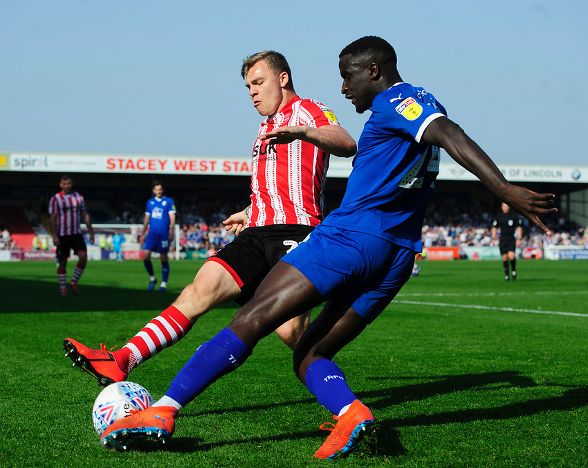 Tranmere Rovers' Zoumana Bakayogo under pressure from Lincoln City's Harry Anderson<br /> <br /> Photographer Chris Vaughan/CameraSport<br /> <br /> The EFL Sky Bet League Two - Lincoln City v Tranmere Rovers - Monday 22nd April 2019 - Sincil Bank - Lincoln<br /> <br /> World Copyright © 2019 CameraSport. All rights reserved. 43 Linden Ave. Countesthorpe. Leicester. England. LE8 5PG - Tel: +44 (0) 116 277 4147 - admin@camerasport.com - www.camerasport.com