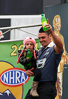 Feb 9, 2014; Pomona, CA, USA; NHRA pro stock driver Shane Tucker holds his daughter as he steps through the door onto the ceremonies of introduction onto the stage during the Winternationals at Auto Club Raceway at Pomona. Mandatory Credit: Mark J. Rebilas-