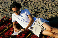 Woman lying on the beach reading a novel, Camargue, France.