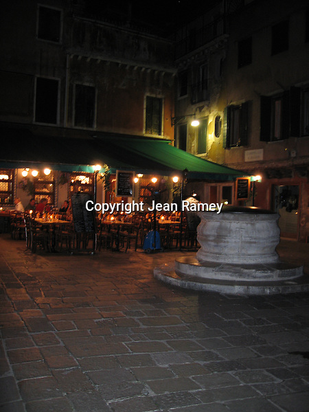 An old well on the piazza keeps a local trattoria company for the evening, Venice
