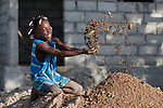 A year after Hurricane Matthew destroyed much of the village of Citerne Remy in Haiti's poverty-wracked northwest, 10-year old Adline Francoise plays in a pile of sand used in the construction of a new house being built by Church World Service, a member of the ACT Alliance.<br /> <br /> Parental consent obtained.