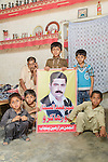 Children hold a poster with a photograph of the leader of the landless peasant movement in Okara, the Anjuman-e-Mazareen (AMP), Mehr Abdul Sattar. Abdul Sattar was arrested in a police and Army Rangers raid on his village 4/4L on May 16th 2016. He was charged with concocted and fake charges of  'terrorism' and thrown into solitary confinement. He remains behind bars as lawyers and activists fight to have him released. Abdul Sattar has lead this movement for over sixteen years and the Pakistani military brass is getting increasingly frustrated, and resorting to greater violence and unjust use of the law, to attempt to break the movement.