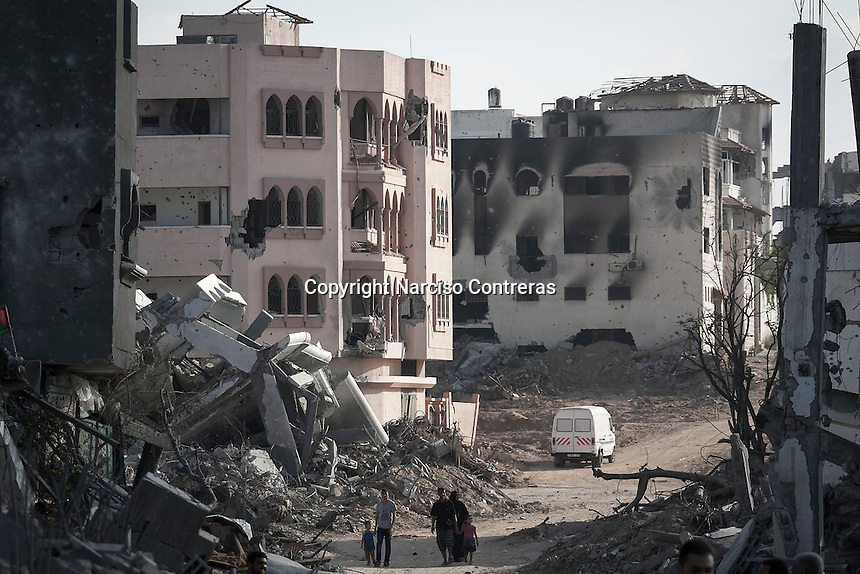 """In this Friday, Aug. 15, 2014 photo, Palestinian civilians walk by house buildings destroyed by israeli airstrikes and artillery shelling during the """"Protective Edge"""" military operation in Shayaja neighborhood in Gaza City. After a five days truce was declared on 13th August between Hamas and Israel, civilian population went back to what remains from their houses and goods in Gaza Strip. (Photo/Narciso Contreras)"""