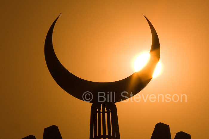 A photo of the sun shining on a silhouetted Muslim crescent at the Faisal Mosque in Islamabad