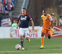 New England Revolution midfielder Diego Fagundez (14) brings the ball forward as Houston Dynamo midfielder Boniek Garcia (27) closes. In a Major League Soccer (MLS) match, the New England Revolution (blue/white) defeated Houston Dynamo (orange), 2-0, at Gillette Stadium on April 12, 2014.