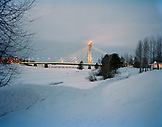 FINLAND, Rovaniemi, view of illuminated Jatkanynttila Bridge on snow covered landscape at dusk.