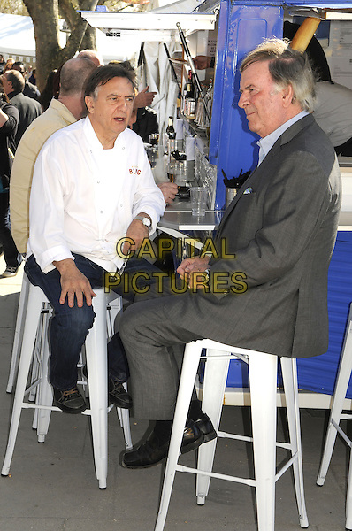 Raymond Blanc & Terry Wogan.being filmed for the BBC at the Real Food Festival, Southbank, London, UK, May 3rd 2013..full length sitting on stool white chef suit jeans  grey gray blue shirt jacket bar .CAP/PP/BK.©Bob Kent/PP/Capital Pictures