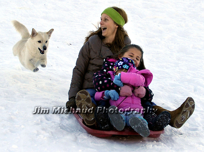 Chrissy Bedrossian, rear,  laughs as she spots her 5-year-old Pomeranian,  Corgi mix named Tucker flying after her while sliding with granddaughter Madison Taylor, 3, foreground and neighbor Angely Camilo, 7, all of Manchester Conn., at Center Park in Manchester, taking advantage of the snow cover that is predicted to melt away due warmer weather this week. (AP Photo / Journal Inquirer, Jim Michaud)
