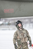 A pilot inspects his helicopter prior to a mission. British Merlin helicopter practice in the Arctic,  near Bardufoss, Norway. <br /> <br /> 845 Naval Air Squadron is a squadron of the Royal Navy's Fleet Air Arm. Part of the Commando Helicopter Force, it is a specialist amphibious unit operating the Leonardo Commando Merlin Mk3 helicopter and provides troop transport and load lifting support to 3 Commando Brigade Royal Marines.<br /> <br /> ©Fredrik Naumann/Felix Features