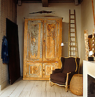 Layers of paint have been scraped from this huge antique cupboard revealing the golden wood beneath