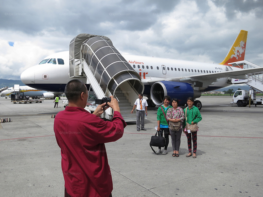 A gentleman dressed in traditional Buddhist costume, takes a snap of his family, as they board the plane at Kathmandu airport for Paro, with Drukair, Nepal to Bhutan..Bhutan the country that prides itself on the development of 'Gross National Happiness' rather than GNP. This attitude pervades education, government, proclamations by royalty and politicians alike, and in the daily life of Bhutanese people. Strong adherence and respect for a royal family and Buddhism, mean the people generally follow what they are told and taught. There are of course contradictions between the modern and tradional world more often seen in urban rather than rural contexts. Phallic images of huge penises adorn the traditional homes, surrounded by animal spirits; Gross National Penis. Slow development, and fending off the modern world, television only introduced ten years ago, the lack of intrusive tourism, as tourists need to pay a daily minimum entry of $250, ecotourism for the rich, leaves a relatively unworldly populace, but with very high literacy, good health service and payments to peasants to not kill wild animals, or misuse forest, enables sustainable development and protects the country's natural heritage. Whilst various hydro-electric schemes, cash crops including apples, pull in import revenue, and Bhutan is helped with aid from the international community. Its population is only a meagre 700,000. Indian and Nepalese workers carry out the menial road and construction work.