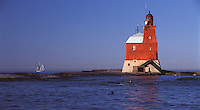 A sailboat passes Porkkala (Kallbådan) lighthouse in the light winds of early morning with curious seals spectating -Gulf of Finland