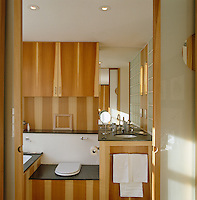 The cupboards and surfaces of this bathroom are covered in wood veneer which creates a striped effect