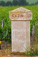 A stone gate post inscribed with Chateau Gazin, vineyard in the background Pomerol Bordeaux Gironde Aquitaine France