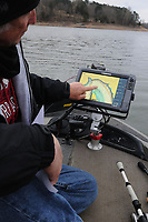 NWA Democrat-Gazette/FLIP PUTTHOFF <br /> Channel swings are bends in a lake that often hold fish all year long. Wiegmann looks Feb. 24 2017 at a map of a channel swing on the upstream end of Beaver Lake.