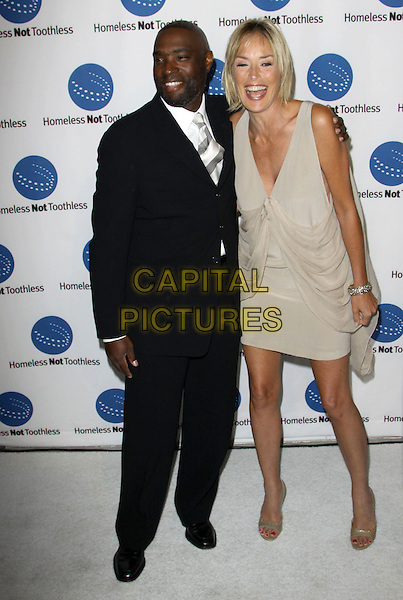 ANTWONE FISHER & SHARON STONE.A Smile For Every Child Gala held At Shangri-La Hotel, Santa Monica, California, USA..September 10th, 2009.full length shoes gold beige sleeveless dress black suit low cut neckline draped open toe shoes mouth open laughing .CAP/ADM/KB.©Kevan Brooks/AdMedia/Capital Pictures.
