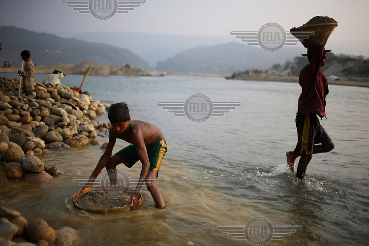 Child worker collecting stone. At least 10,000 people, including 2,500 women and over 1,000 children, are engaged in stone and sand collection from the Bhollar Ghat on the banks of the Piyain river. Building materials such as stone and sand, and the cement which is made from it, are in short supply in Bangladesh, and commands a high price from building contractors. The average income is around 150 taka (less than 2 USD) a day...