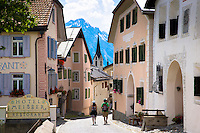 Tourists pass Hotel Meisser in Engadine Valley village of Guarda, painted stone 17th Century buildings, Switzerland
