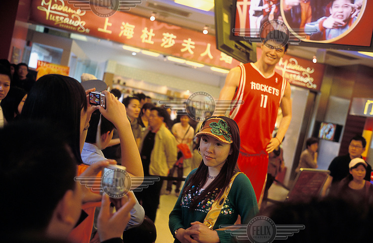 A shopper takes a picture of her friend next to a waxwork figure of Yao Ming, an NBA basketball star, with a digital camera outside Madame Tussauds.