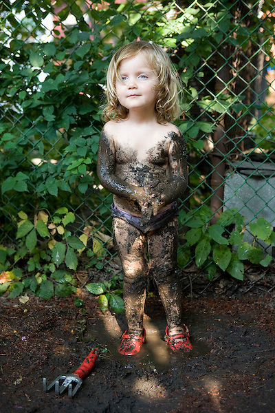 little girl has playfully covered herself in mud