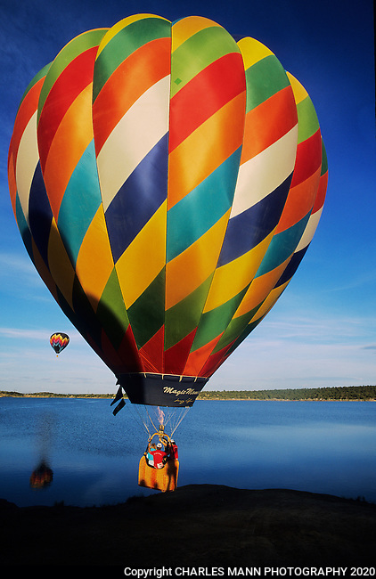 A colorful balloon takes to the sky over a local lake at the Farmington Balloon Festival in Farmington, New Mexico