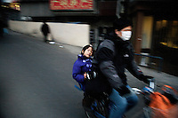 People ride bikes in a small alley in the central university district of Nanjing, Jiangsu Province, China.